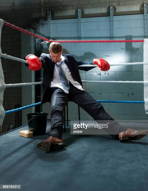 business man knocked out in corner of box ring - face off sports play stock photos and pictures
