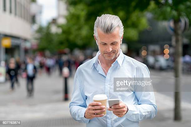 Business man listening to music on his phone