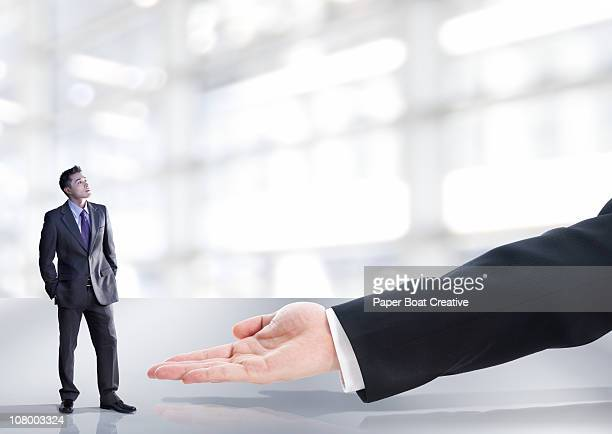 Business man looking at a giant hand