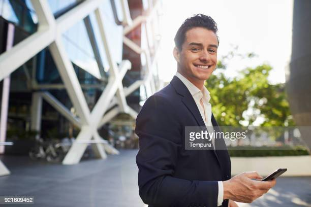 Business man looking at camera and holding a smart phone.