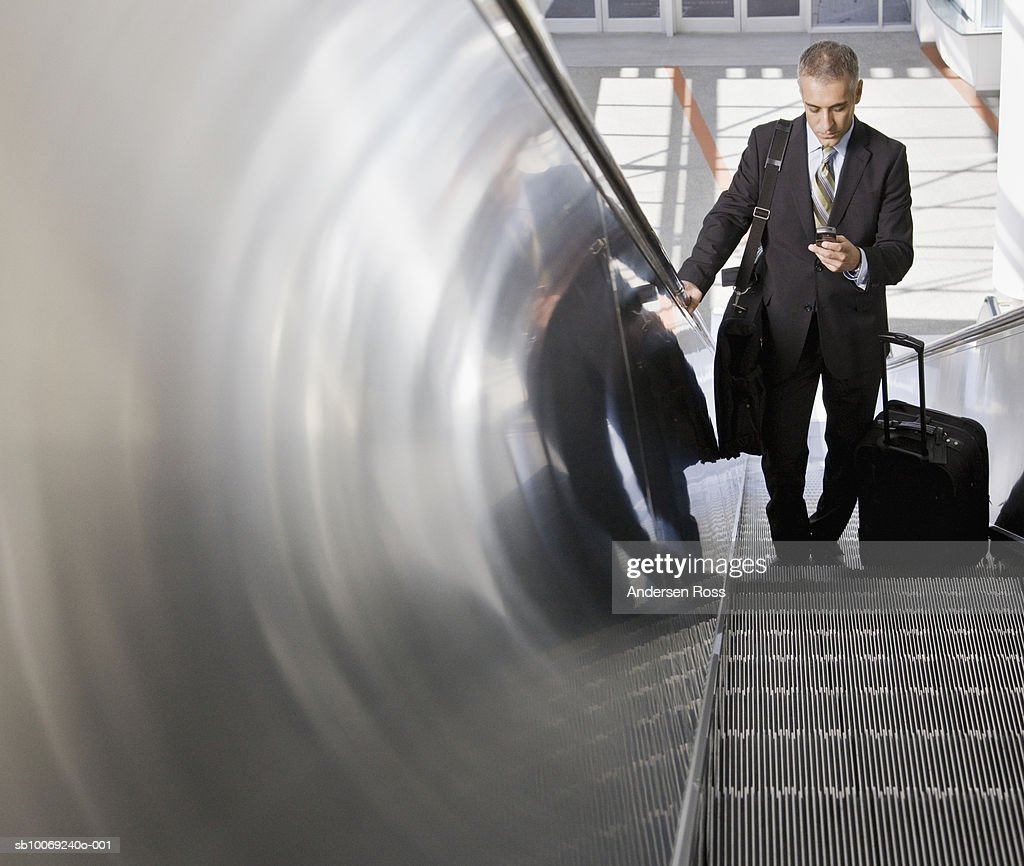 Business man looking at mobile phone on escalator : Stockfoto