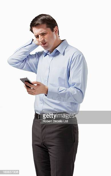 business man looking at smart phone in confusion