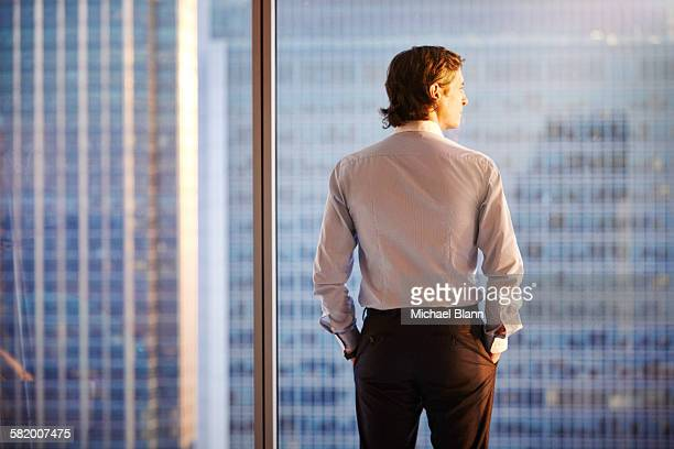 business man looking at sun from city apartment - brown hair stock pictures, royalty-free photos & images