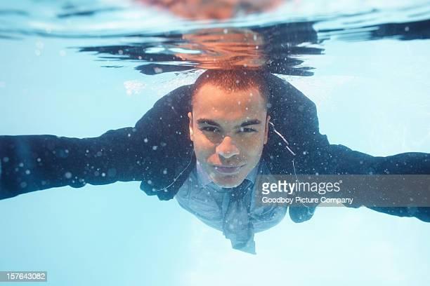 Un hombre de negocios mirando a usted como él swims en agua