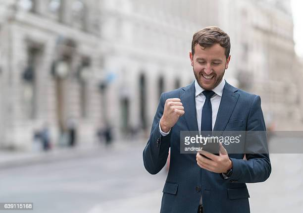 Business man looking excited checking his cell phone