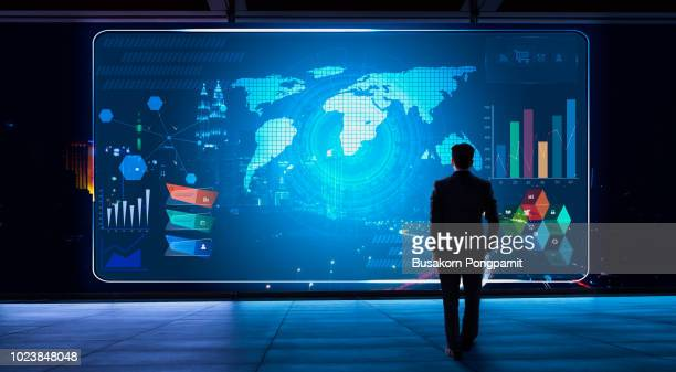 business man looking financial graph icon on futuristic virtual screen with technology - projektion stock-fotos und bilder