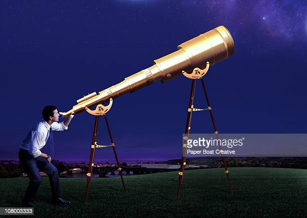 business man looking through a giant telescope