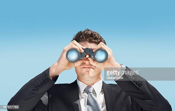 Business man looking through a pair of binoculars
