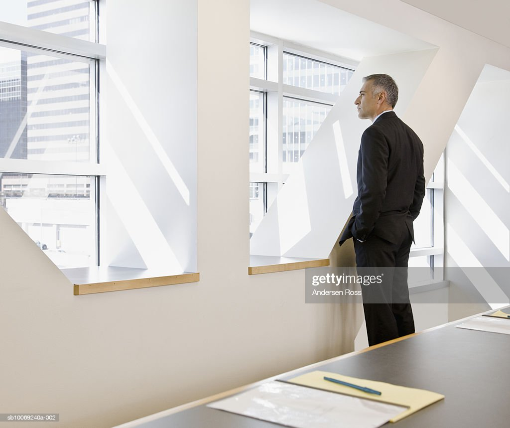 Business man looking through window, side view : Stockfoto