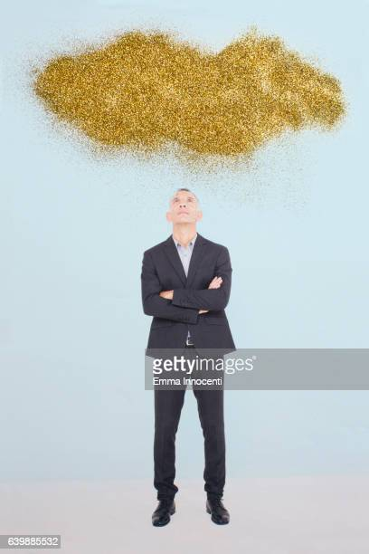 Business man looking up at a gold cloud
