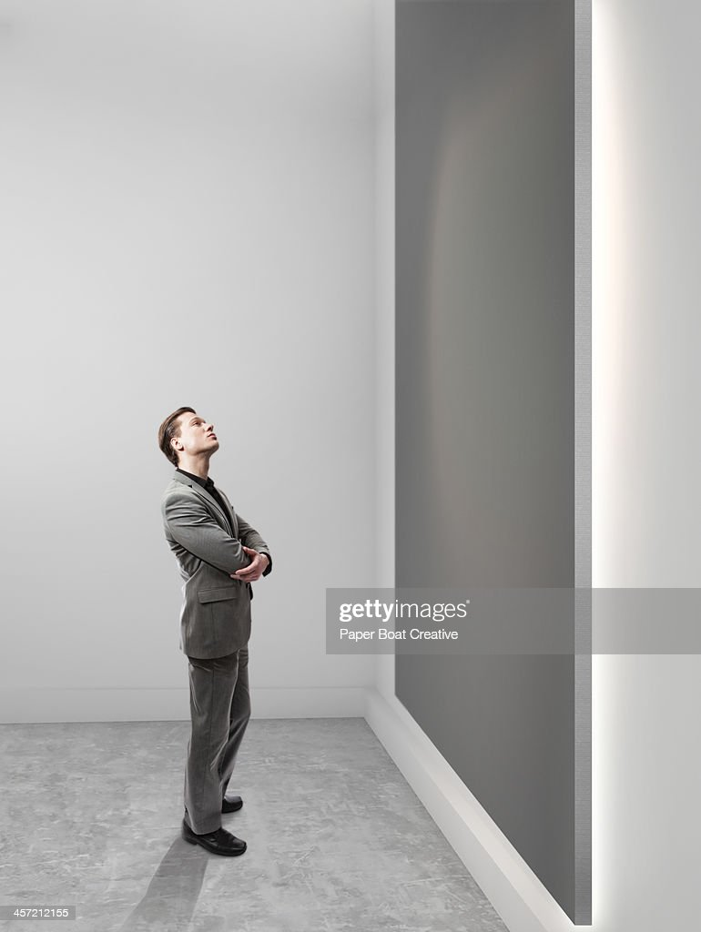 Business man looking up at blank grey canvas : Stock-Foto