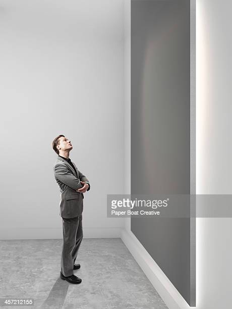 business man looking up at blank grey canvas - vertikal stock-fotos und bilder
