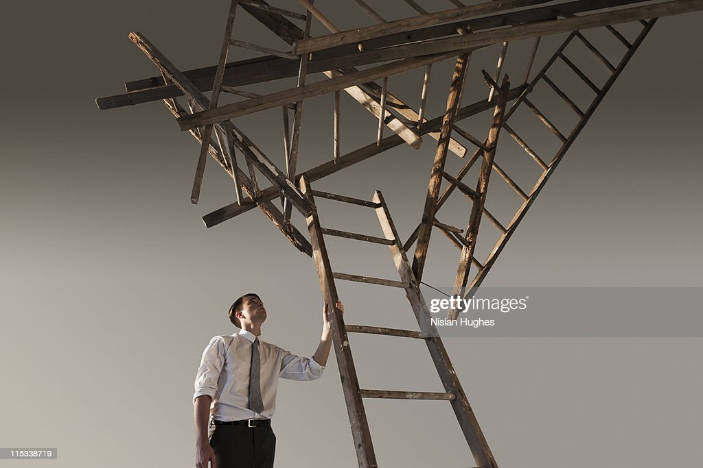 business man looking up at cluster of ladders : Stock Photo