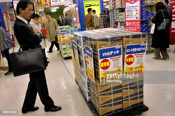 A business man looks at a stack of boxed VCRs in a store in central Tokyo Tuesday March 29 2005 Confidence among Japan's large manufacturers failed...