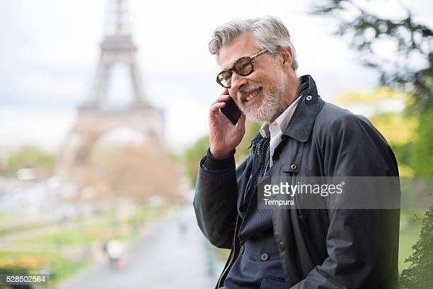 Hombre de negocios haciendo una llamada telefónica cerca de la Torre Eiffel.