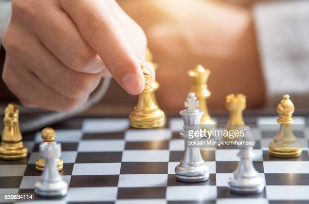 business man moving chess figure with team behind - pursuit concept stock photos and pictures