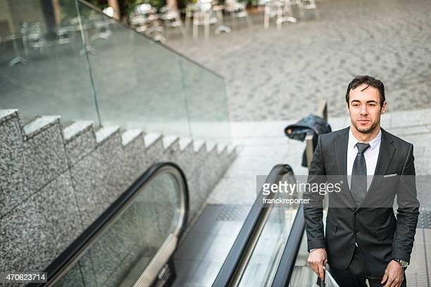 Business-Mann, die auf den Rolltreppen