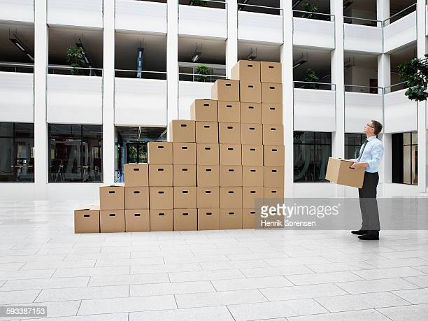 Business man next to a stack of boxes,