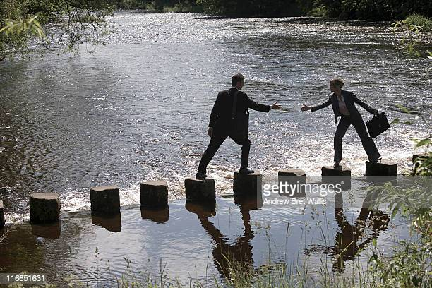 Business man offers woman support to cross a river