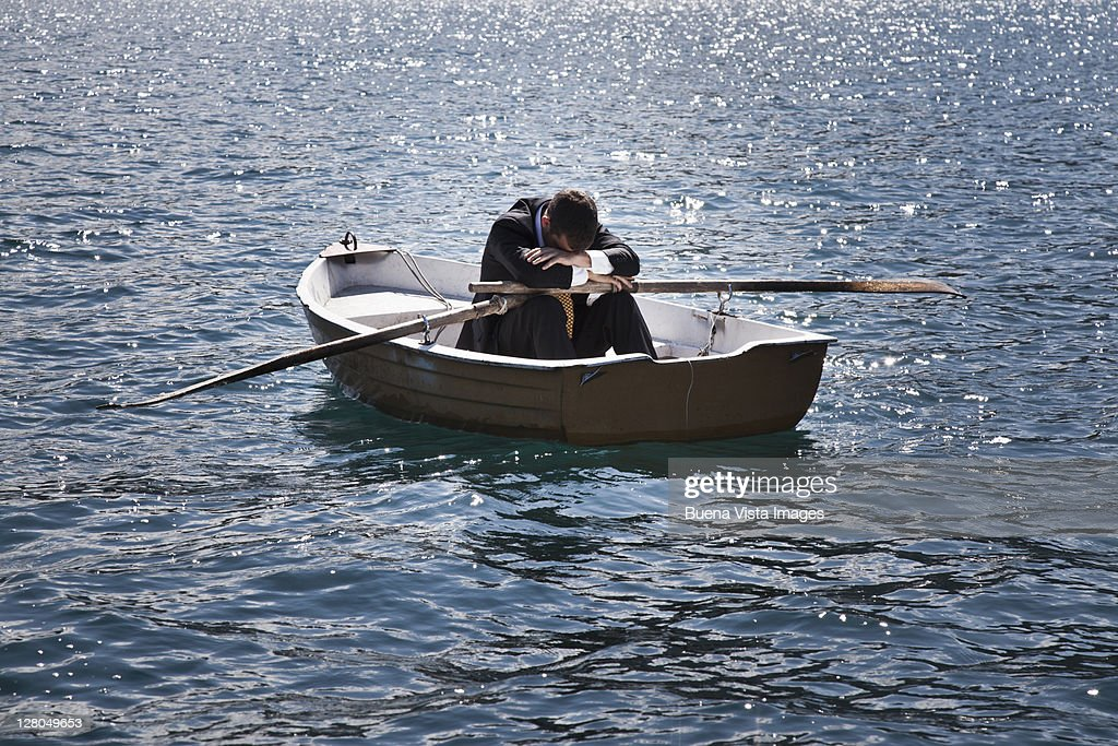 Business man on a boat in the ocean : Stock Photo