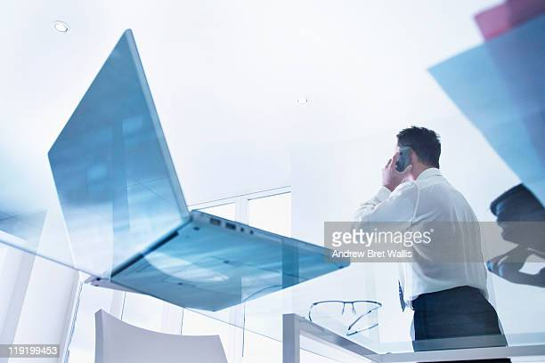 Business man on mobile viewed through glass desk