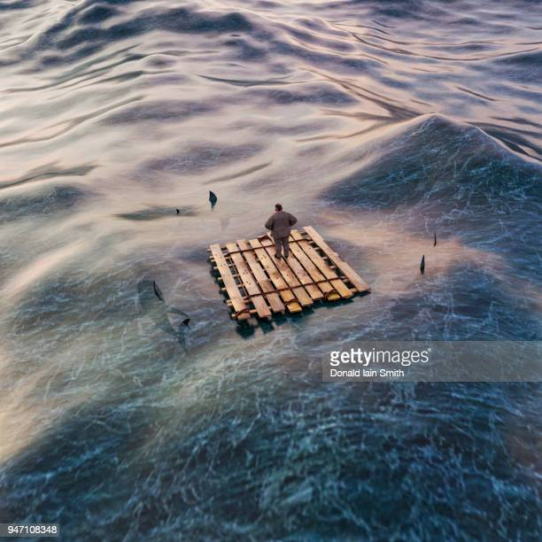 business man on raft at sea surrounded by sharks, aerial view looking down - lifeboat stock pictures, royalty-free photos & images