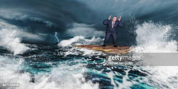 Business man on raft in storm at sea