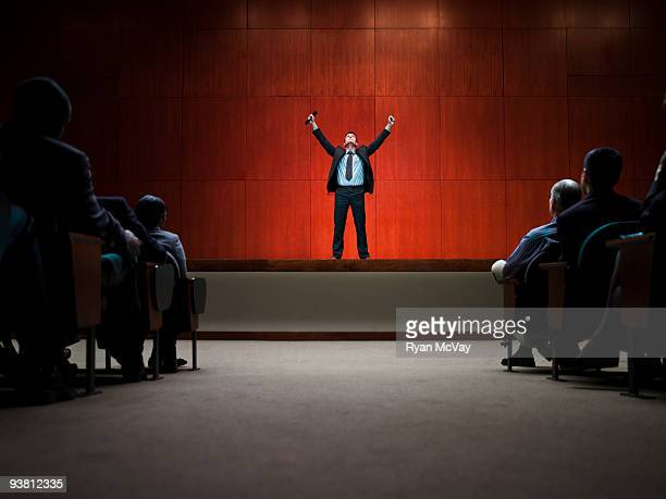 Business man on stage with arms raised
