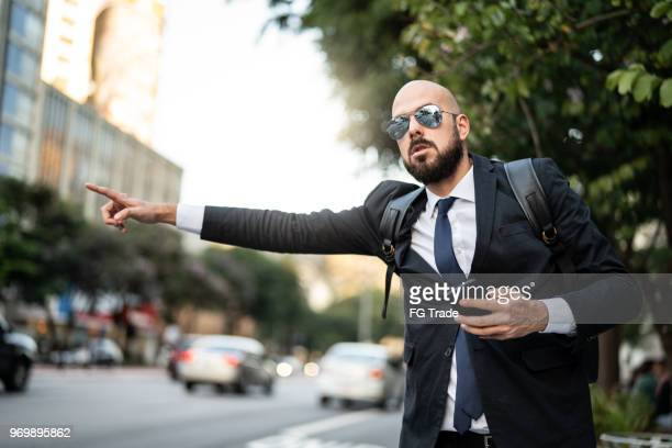 business man on the move waiting for your transport - hail stock pictures, royalty-free photos & images