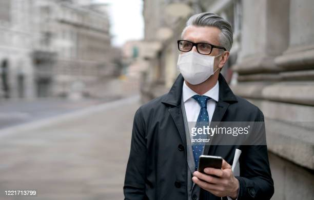 business man on the street wearing a facemask to avoid covid-19 and using app on his cell phone - business stock pictures, royalty-free photos & images