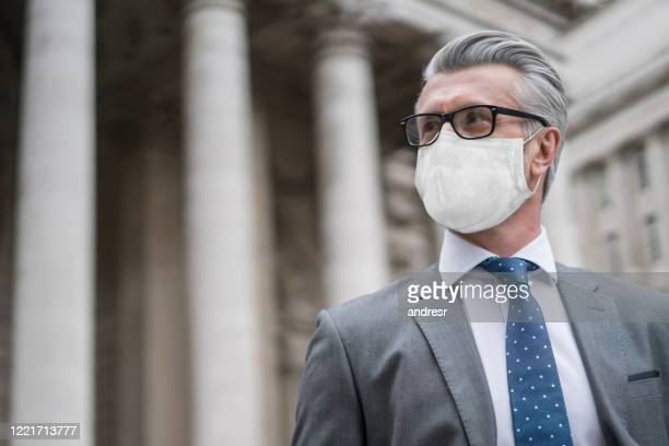 business man on the street wearing a facemask to avoid covid-19 - judge stock pictures, royalty-free photos & images