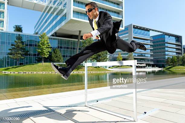 business man over hurdle near offices - hurdling stock photos and pictures