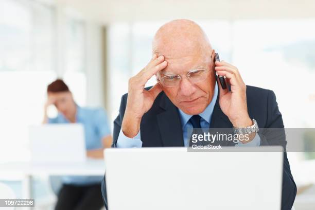 Business man over the cellphone while working on a laptop