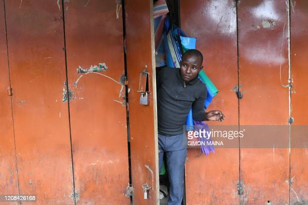 TOPSHOT A business man peeks out of his shop's door while closing his shop before the beginning of a curfew which was ordered by Kenyan President...
