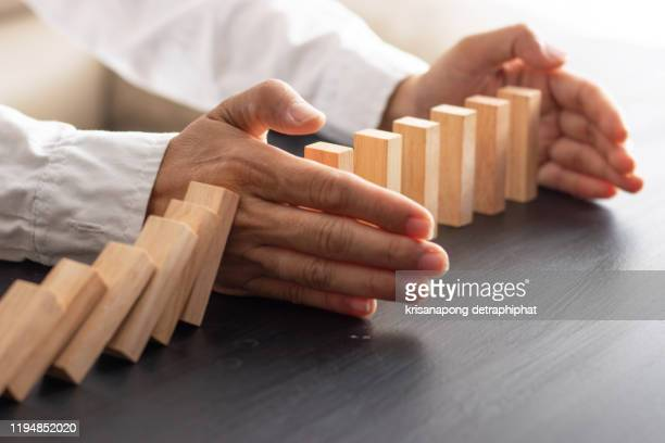 business man placing wooden block on a tower concept risk control, planning and strategy in business.alternative risk concept,risk to make buiness growth concept with wooden blocks - リスク管理 ストックフォトと画像