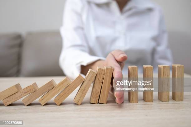 business man placing wooden block on a tower concept risk control, planning and strategy in business.alternative risk concept,risk to make buiness growth concept with wooden blocks - risk stock pictures, royalty-free photos & images