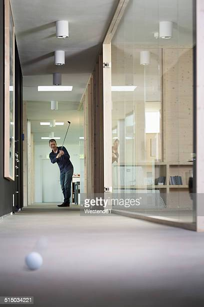 Business man playing golf in corridor of modern office