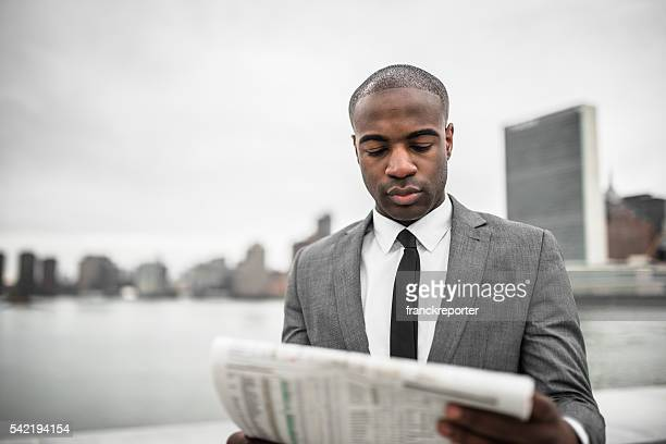 business man portrait reading the newspaper in nyc
