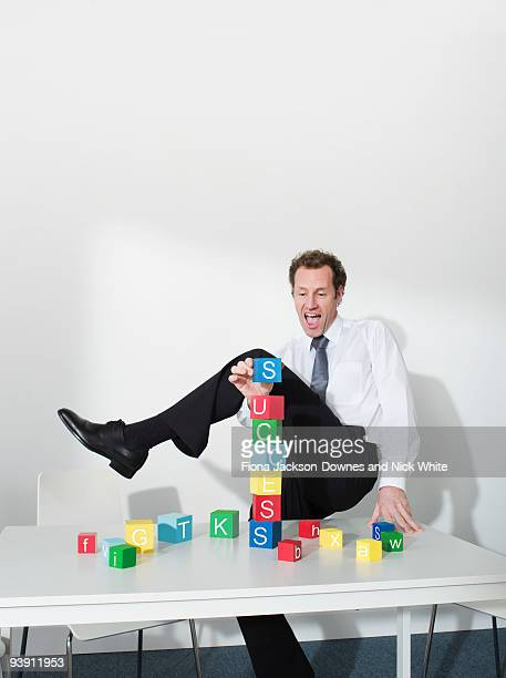 Business man puts last block on tower
