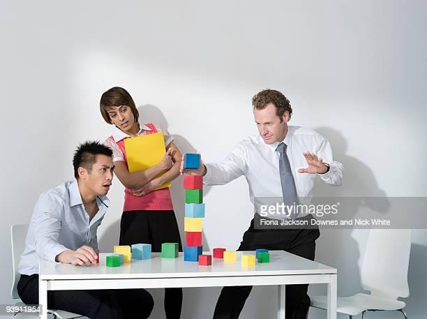 Business man puts last block on tower