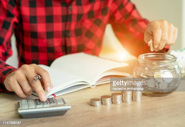 business man putting coin in glass bottle saving bank and account for his money all in finance accounting concept. - wages stock pictures, royalty-free photos & images