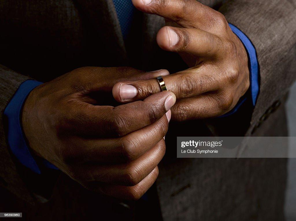 Business man putting on wedding band : Stock Photo