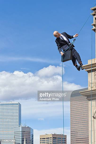 Business Man Rappelling Off High Building
