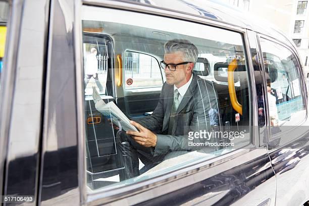 Business man reading a newspaper in a taxi