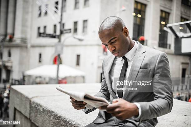 business man reading a newspaper on nyc