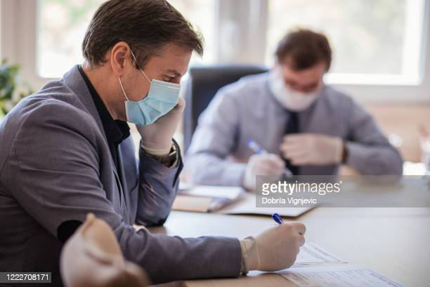 business man reading his employee's report and frowning while wearing protective mask - state of emergency stock pictures, royalty-free photos & images