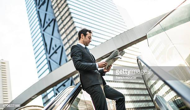 ビジネスの男性の読書新聞、エスカレーター