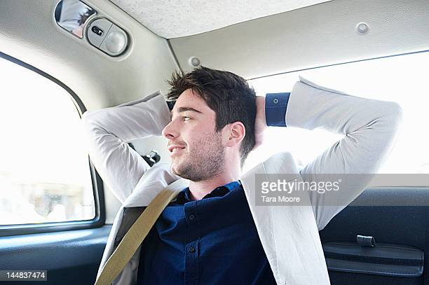 business man relaxing in taxi and smiling - newtechnology stock pictures, royalty-free photos & images