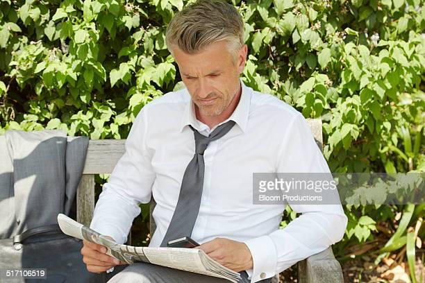 Business man relaxing reading a newspaper