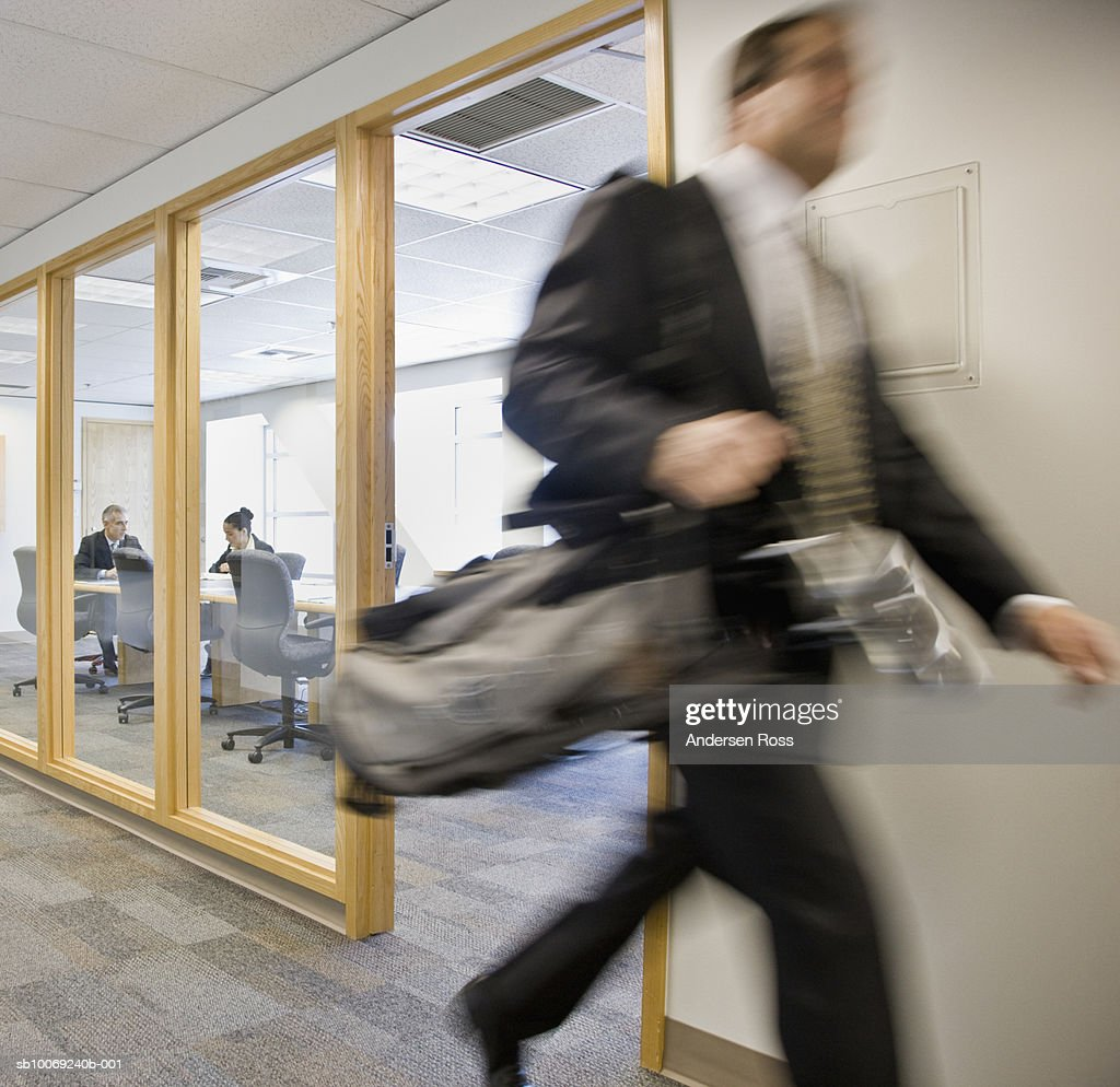 Business man running with golf clubs by conference room : Stockfoto